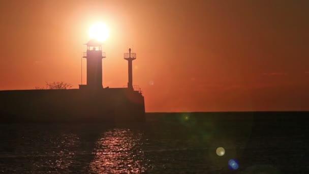 Sonnenaufgang gegen ein Leuchtfeuer in Jalta
