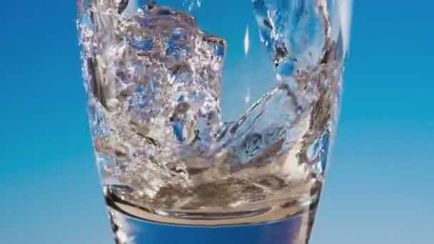 Blu acqua scorre nel bicchiere formando bolle e spruzzi