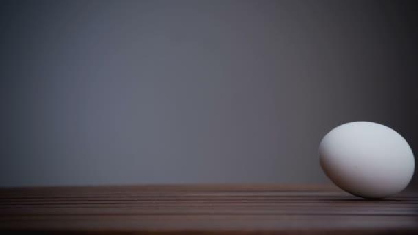 Egy tojás gurul az asztalon. Lassú mozgás
