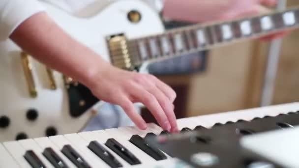 Mann spielt Gitarre und Keyboard