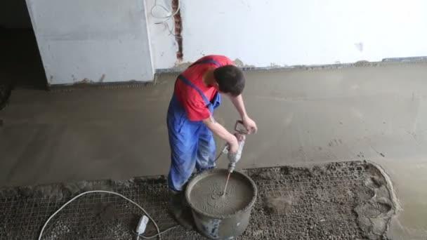 Worker preparing concrete grout for floor