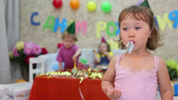 Little girl blows in party blowers