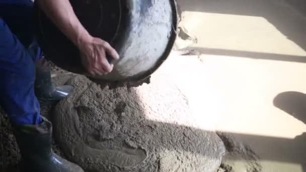 Pracovník v holínkách Lije kýbl