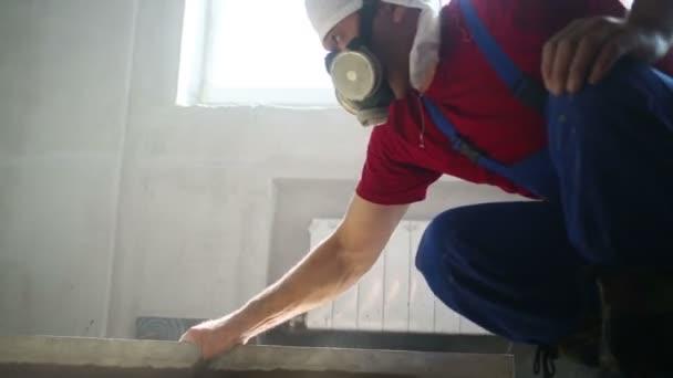 Pracovník zarovná betonovou podlahu v místnosti