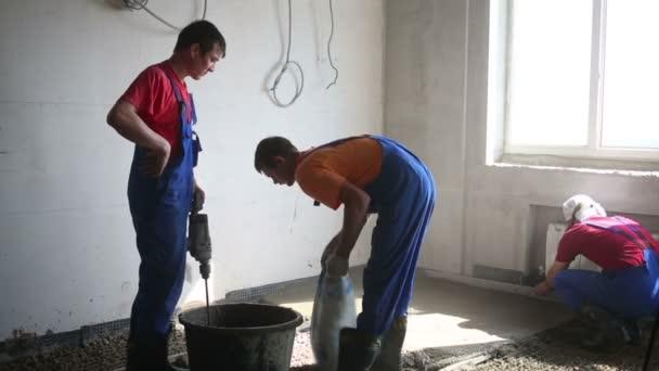 Tři pracovníci připravit směs pro podlahu