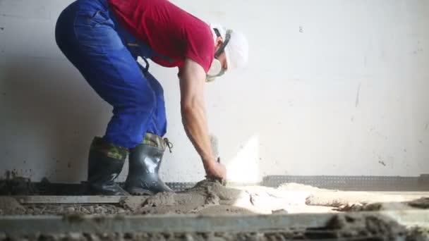 Pracovník dělá betonovou podlahu v místnosti