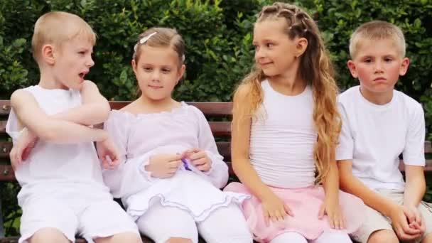 Jungen und Mädchen sitzen auf Bank