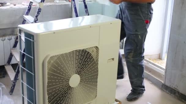 Junger Mann in der Nähe von Klimaanlage