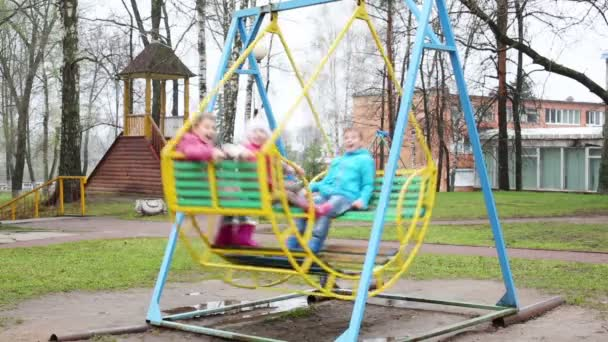 Boy and two girls on swings