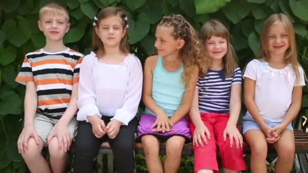 děti sedí na lavičce