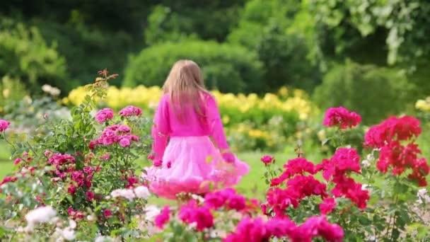 Rücken eines kleinen Mädchens in rosa üppigem Rock, das zwischen Blumen wandelt