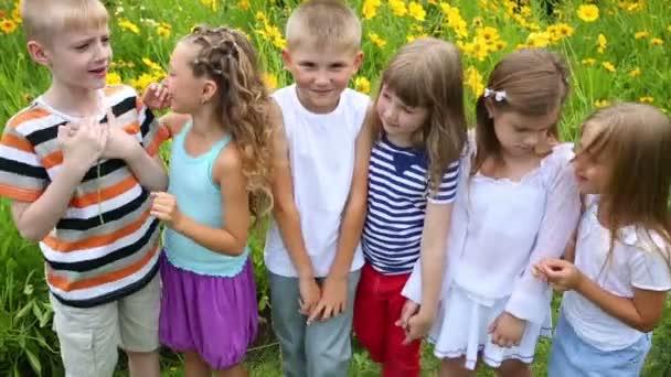 Kinder stehen neben Blumenbeet