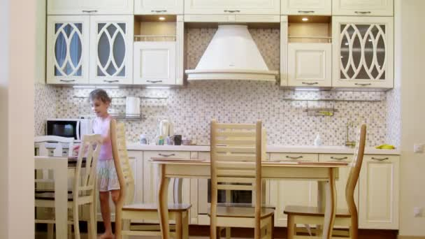 Girl sets the table in light kitchen.