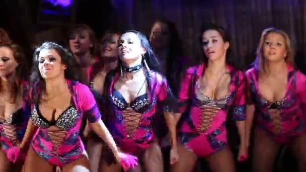 happy showgirls in purple costumes