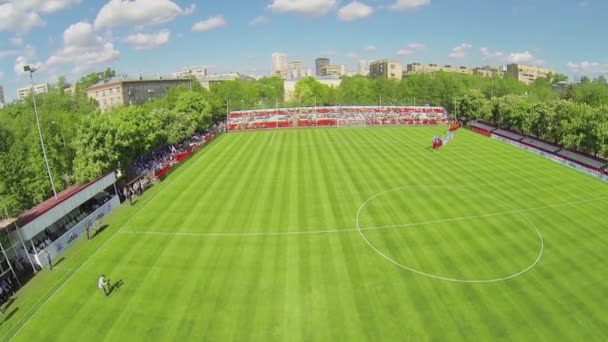 Teams walk by soccer field