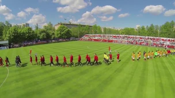 Players walk by soccer field