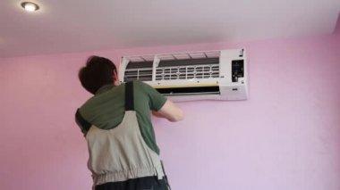 Professioneel volwassen model installeert de airco op de kamer
