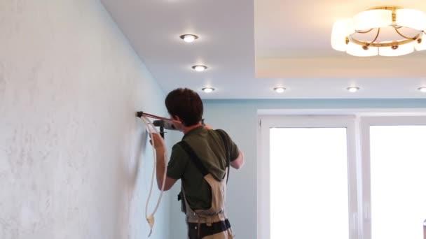 Arbeiter bohrt ein Loch in die Wand einer modernen neuen Wohnung