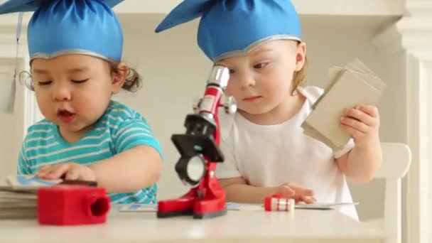 Small babies in blue graduation hats adjust microscope on table
