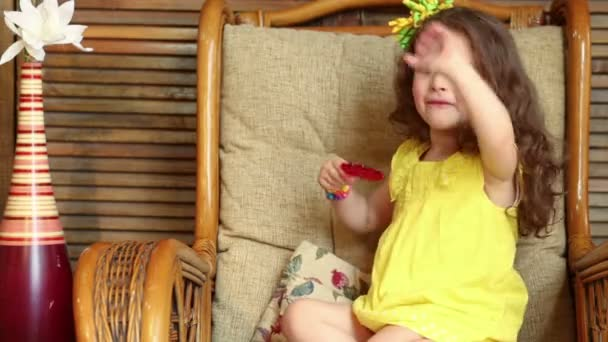 Little curly girl is licking a lollipop and waving ones hand.