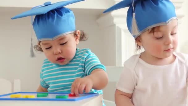 two cute babies in graduation hats play with letters on magnets