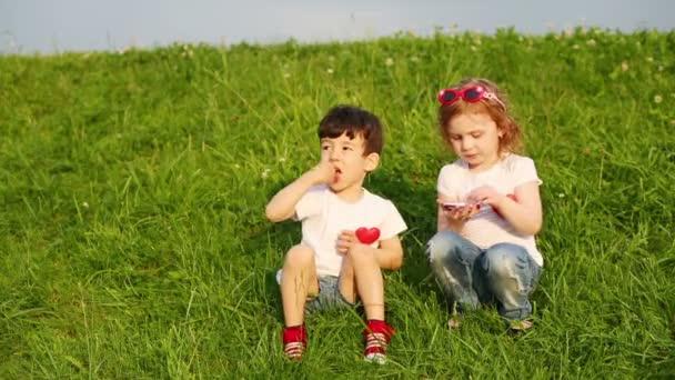 Two children  sit on grass