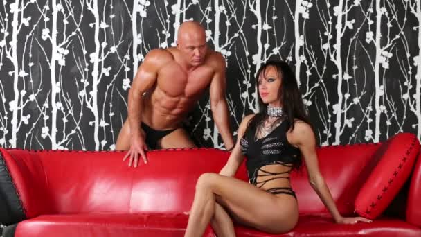Woman sits on red sofa, muscular man stands behind leaning at it.