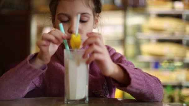 Malá holka pije mléko koktejl, sedí u stolu v kavárně