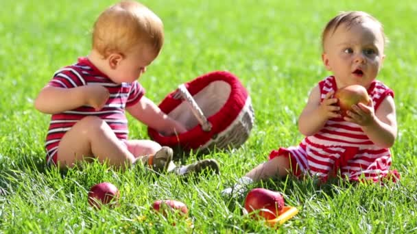 Two babies in red eat  apples