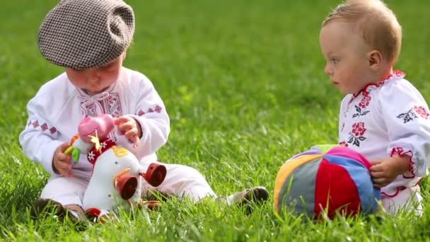 Dvě roztomilá miminka v lidových šatech si hrají s hračkou a koulí