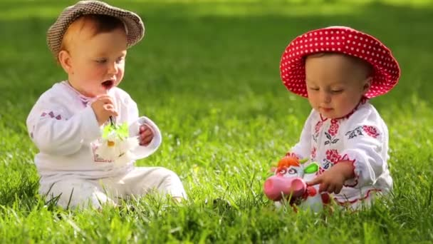 Two babies in folk clothes and hats play with toy funny cow