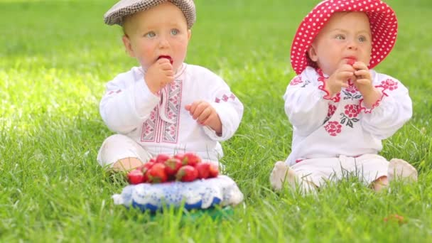Two cute babies in folk clothes and hats eat strawberries