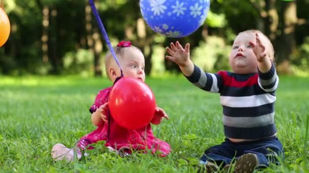 Balloons hang on clothesline and two babies play with its