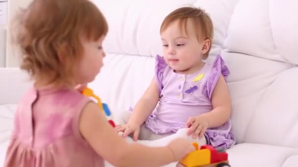 Two little girls in dresses play with toy cars on white sofa