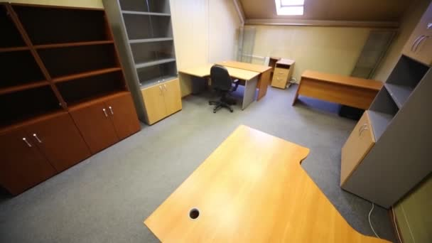 Spacious modern office room with empty bookcases and work desks