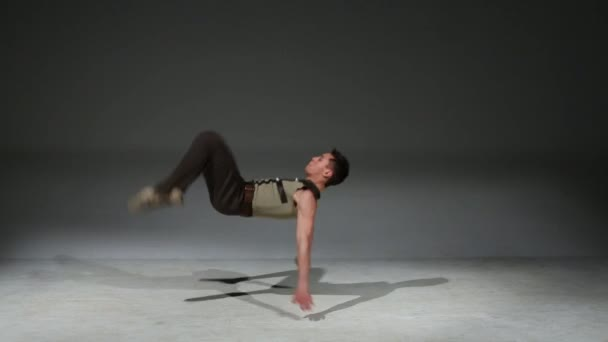 Acrobat man in medieval costume does exercise in studio