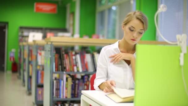 dívka seděla u stolu a četla knihu v knihovně