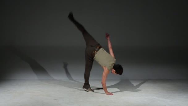Asian acrobat man in medieval costume jumps in studio