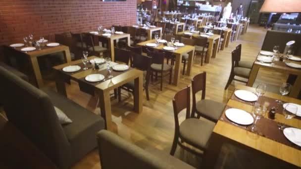 Prostorná hala s obsluhatelnými stoly a stěnami cihel v restauraci.