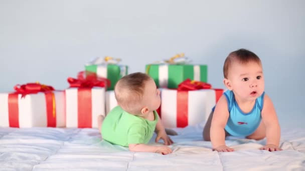 Two little babies near many large gift boxes in studio