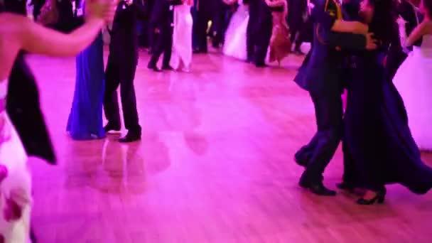Mnoho šťastných tančící lidí v růžovém světle na krásném plese
