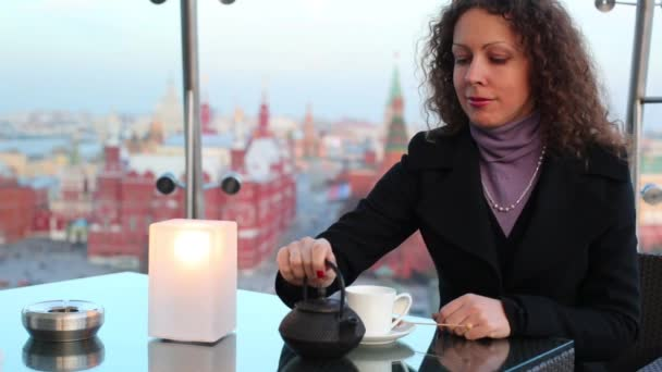 Woman pours tea from a teapot and drinks tea in restaurant