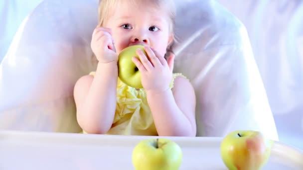 Malá holčička křupky velké jablko, sedět na židličce.
