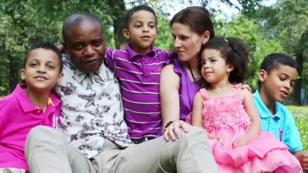 Felice famiglia di sei canta e abbracciarsi in un parco di estate