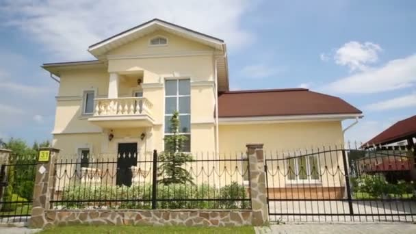 Modern two storey cottage with wrought fence at summer day