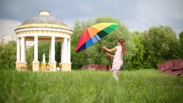 Usmívající se dívka tančí s barevný deštník na zelený trávník