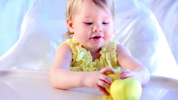 girl eats apple and plays with another one, sitting on highchair.