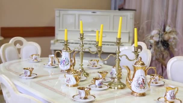 Marble table with set of porcelain dishes and candles