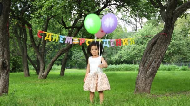 Little girl with three balloons standing in a park
