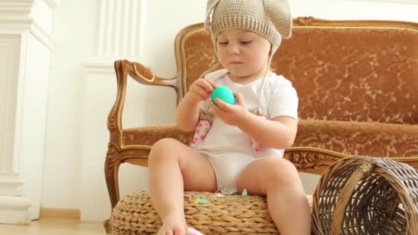 Baby girl in hat with ears of rabbits sits and cleans green egg